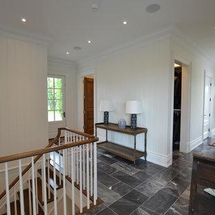 Exemple d'un couloir chic de taille moyenne avec un mur blanc, un sol en marbre et un sol noir.