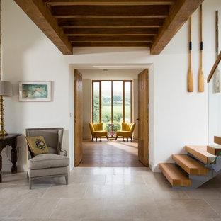 Inspiration pour un couloir rustique avec un mur blanc et un sol gris.