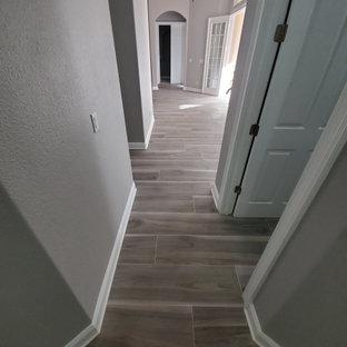 Свежая идея для дизайна: коридор среднего размера в стиле модернизм с серыми стенами, полом из керамогранита и серым полом - отличное фото интерьера