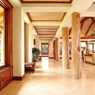 ハワイの大きいトロピカルスタイルのおしゃれな廊下 (トラバーチンの床、ベージュの壁、ベージュの床) の写真