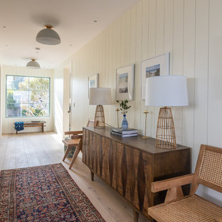 Large beach style hallway in Los Angeles with white walls, light hardwood floors and brown floor.