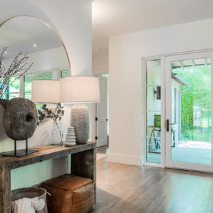 Example of a mid-sized trendy light wood floor hallway design in Dallas with white walls