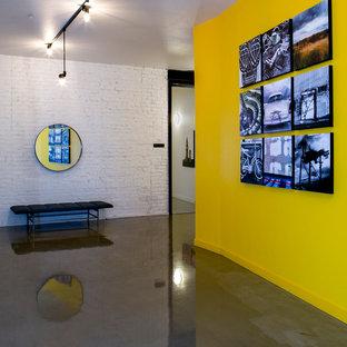 Immagine di un grande ingresso o corridoio industriale con pareti gialle e pavimento in cemento