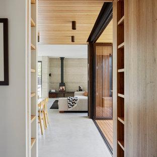 Cette photo montre un couloir tendance de taille moyenne avec un mur blanc, béton au sol et un sol gris.