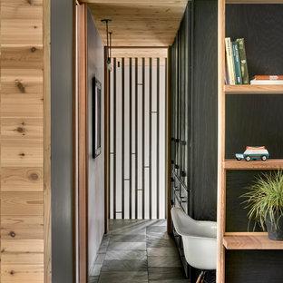 На фото: коридор среднего размера в стиле рустика с белыми стенами, полом из сланца, черным полом и деревянными стенами