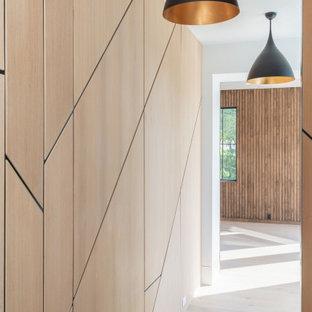 Modern inredning av en stor hall, med beige väggar, ljust trägolv och beiget golv