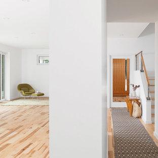 Bild på en mellanstor minimalistisk hall, med gula väggar och ljust trägolv