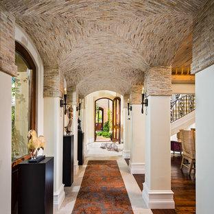 Свежая идея для дизайна: огромный коридор в средиземноморском стиле с бежевыми стенами и полом из травертина - отличное фото интерьера