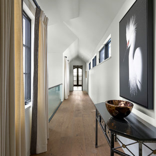 Example of a huge trendy medium tone wood floor hallway design in Denver with white walls