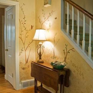 Idéer för att renovera en mellanstor funkis hall, med gula väggar och mellanmörkt trägolv