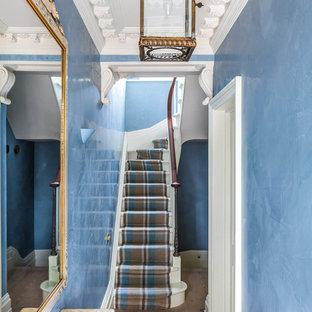 Aménagement d'un petit couloir classique avec un mur bleu, un sol en bois clair et un sol marron.