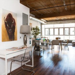 Cette image montre un couloir urbain avec un mur blanc et un sol en bois foncé.