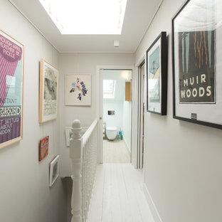 ロンドンのトランジショナルスタイルのおしゃれな廊下 (グレーの壁、塗装フローリング、白い床) の写真