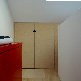 Inspiration pour un petit couloir nordique avec un mur blanc et un sol en contreplaqué.