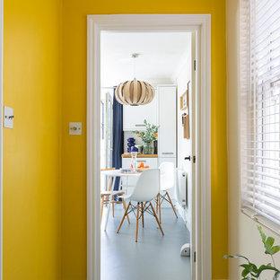 Idée de décoration pour un petit couloir design avec un mur jaune, un sol en vinyl et un sol gris.