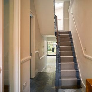 Imagen de recibidores y pasillos tradicionales renovados, de tamaño medio, con paredes beige, suelo de madera oscura y suelo negro