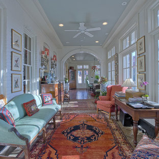 Cette image montre un très grand couloir traditionnel avec un mur blanc et un sol en brique.