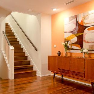 Bild på en retro hall, med orange väggar, mellanmörkt trägolv och orange golv
