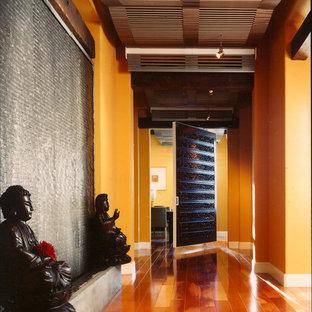 Cette image montre un couloir asiatique avec un mur orange, un sol en bois brun et un sol orange.