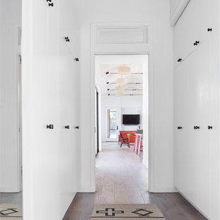 Hallway - scandinavian medium tone wood floor and brown floor hallway idea in Austin with white walls