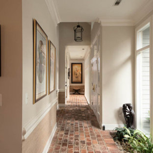 Photo of a mid-sized beach style hallway in Atlanta with multi-coloured walls, brick floors and red floor.