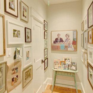 Shabby chic-inspirerad inredning av en hall, med vita väggar och mellanmörkt trägolv