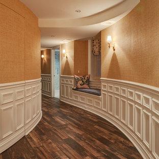 Idee per un grande ingresso o corridoio tradizionale con pareti arancioni, pavimento in gres porcellanato e pavimento marrone