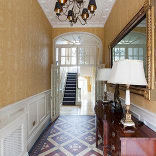 Exempel på en mellanstor klassisk hall, med gula väggar, linoleumgolv och flerfärgat golv