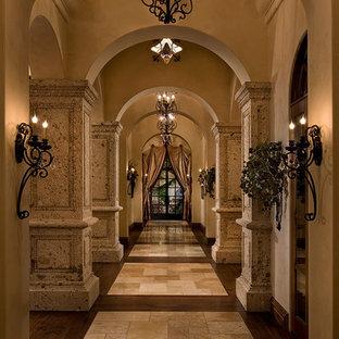 Idée de décoration pour un très grand couloir méditerranéen avec un mur beige et un sol en travertin.