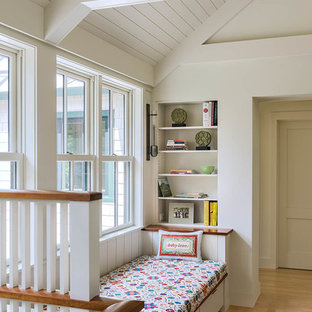 Design ideas for a mid-sized beach style hallway in Portland Maine with white walls and light hardwood floors.
