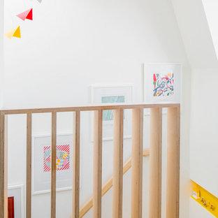 ロンドンの小さいコンテンポラリースタイルのおしゃれな廊下 (白い壁、合板フローリング、茶色い床) の写真