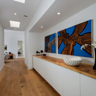 This is an example of a large midcentury hallway in Orange County with white walls, medium hardwood floors and brown floor.