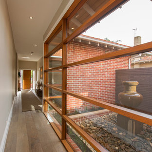 Design ideas for a contemporary hallway in Melbourne with beige walls and medium hardwood floors.
