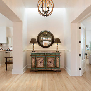Design ideas for a mid-sized traditional hallway in Albuquerque with white walls and light hardwood floors.