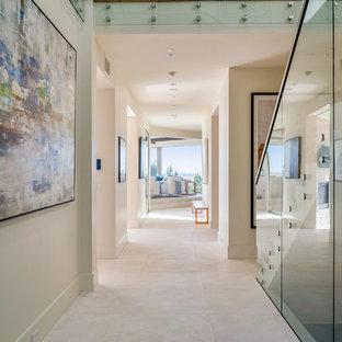 ロサンゼルスの巨大なコンテンポラリースタイルのおしゃれな廊下 (白い壁、ライムストーンの床、白い床) の写真