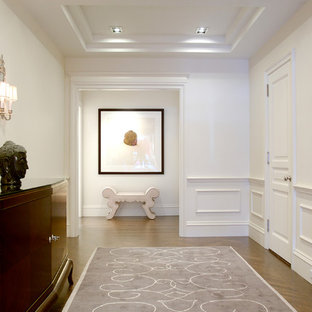 Example of a large transitional medium tone wood floor hallway design in New York with white walls
