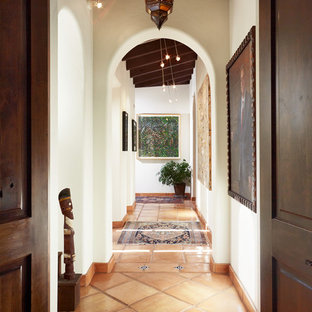 Example of a tuscan terra-cotta floor hallway design in Austin with white walls