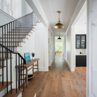 Example of a mid-sized transitional medium tone wood floor and brown floor hallway design in San Francisco with white walls