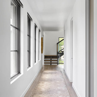 Hallway - large contemporary dark wood floor and brown floor hallway idea in Dallas with white walls