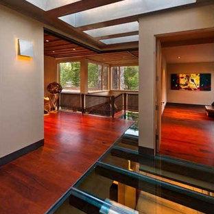 Exemple d'un grand couloir moderne avec un mur marron, un sol en bois brun et un sol marron.