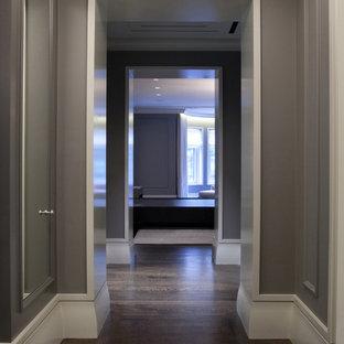 Modern inredning av en mellanstor hall, med grå väggar, mörkt trägolv och brunt golv