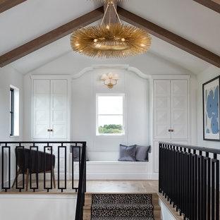 Mediterranean hallway in Minneapolis with white walls, light hardwood floors and beige floor.