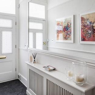 Inredning av en modern liten hall, med vita väggar och svart golv