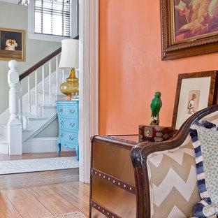 Foto på en mellanstor eklektisk hall, med orange väggar och ljust trägolv