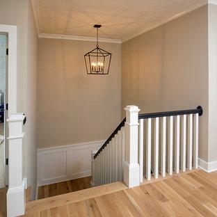 Cette photo montre un couloir nature de taille moyenne avec un mur beige et un sol en bois clair.