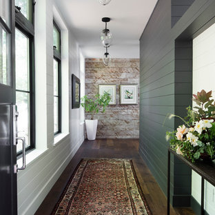 Example of a large farmhouse dark wood floor and brown floor hallway design in Seattle with white walls