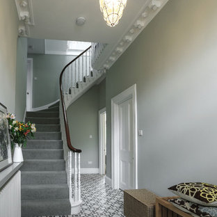 Example of a large trendy concrete floor and multicolored floor hallway design in London with green walls