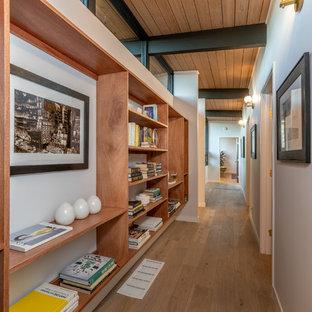 Midcentury hallway in San Francisco with white walls, medium hardwood floors and brown floor.