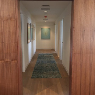 Photo of a mid-sized midcentury hallway in DC Metro with white walls and light hardwood floors.