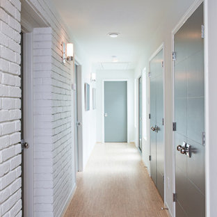 This is an example of a large midcentury hallway in Other with white walls and cork floors.